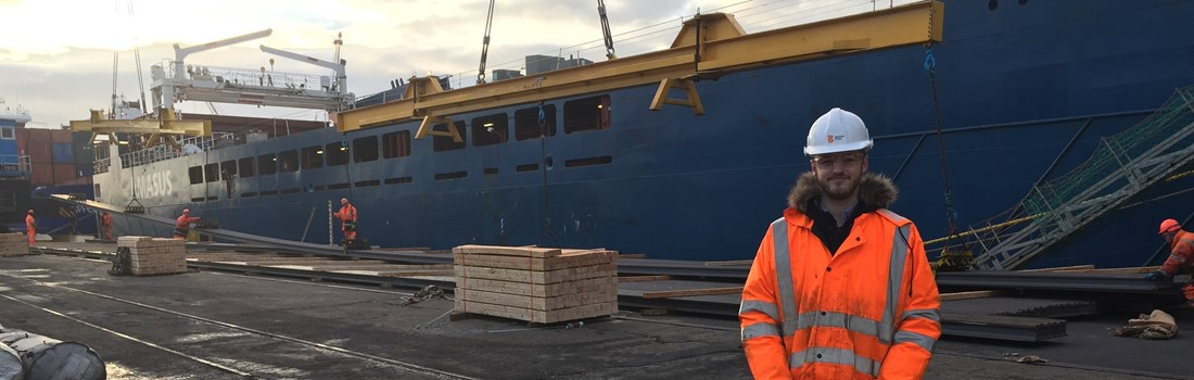 Supply Chain Graduate Keelan Whiteley in front of a docked cargo ship
