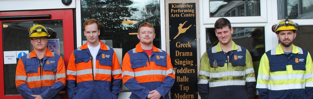 5 apprentices stood outside a building next to a sign advertising Kimberley Performing Arts Centre