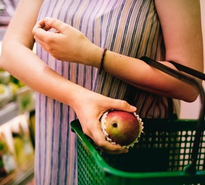A lady at the supermarket putting an apple in her basket